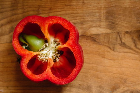 Fresh sweet red pepper cut in half with a growth inside on old wooden background. Overgrown boot Stock Photo