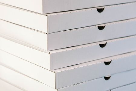A large stack of white empty pizza boxes