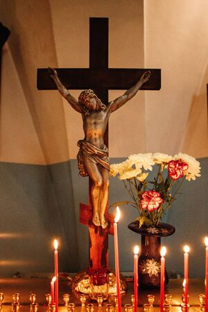 Visit the temple, light candles on a stand, cross crucifix with jesus in focus