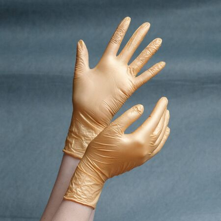 Hands in nitrile gloves of gold color on a gray background with a gradient. Square aspect ratio