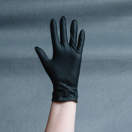 Hand in nitrile glove of black color on a gray background with a gradient. Square aspect ratio