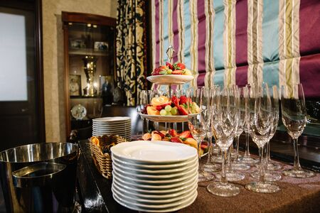 A three-tier modern dish with yellow brass plates and a rod with a ring handle. For desserts or snacks with fresh berries and fruits. Buffet table with plates and ice bucket for champagne