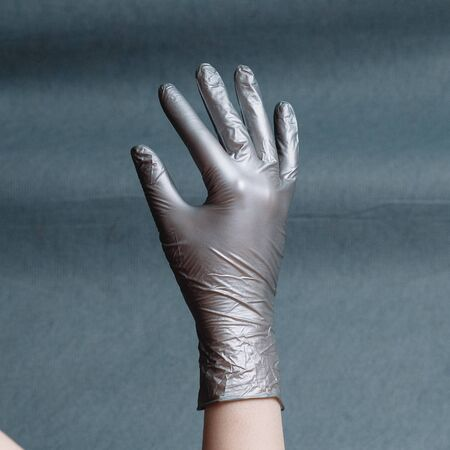 Hand in silver nitrile glove on a gray background with a gradient. Square aspect ratio Фото со стока