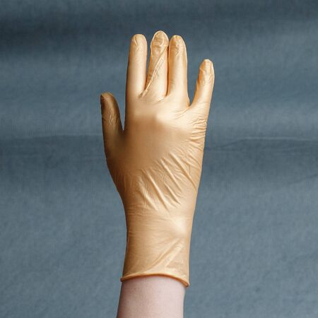 Hand in nitrile glove of gold color on a gray background with a gradient. Square aspect ratio