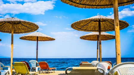Beautiful Seascape With Beach Umbrellas And Sunbeds in Stavros, Greece Stock Photo