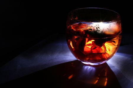 Glowing glass with rose petals inside. Looks like a magical drink. photo