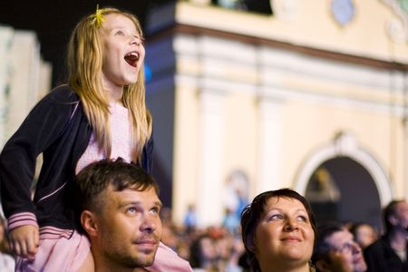 Family with small daughter is enjoying the concert show