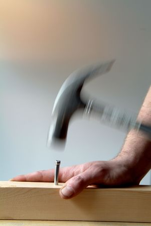 hammering: hammering nail into block of wood Stock Photo