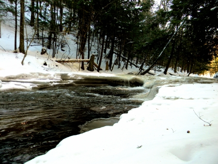 upper peninsula:   photo of a snow covered river flowing through the upper peninsula of Michigan                              Stock Photo