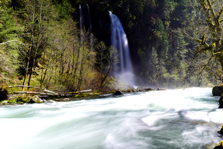 photo of a mystical waterfall emptying into white water below in the outdoors of southern Oregon
