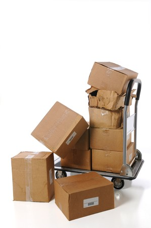 Plain brown boxes stacked and falling off small cart Stock Photo