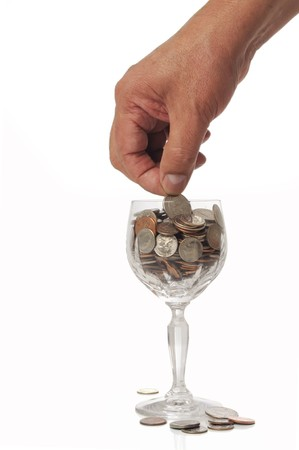 Hand placing quarter in crystal glass full of coins
