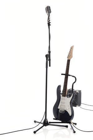 Vintage microphone on stand beside an eletric guitar