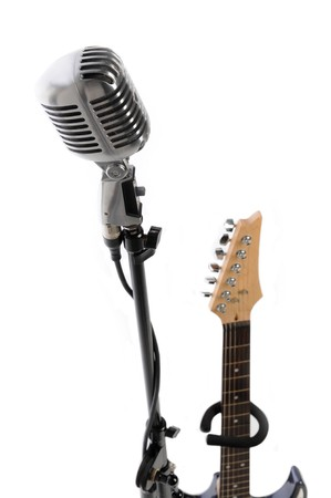 Vintage microphone on stand beside an electric guitar Stock Photo