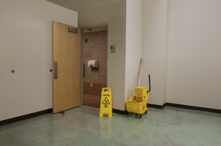 Caution sign, mop and bucket outside open door of a public restroom being cleaned Stock Photo
