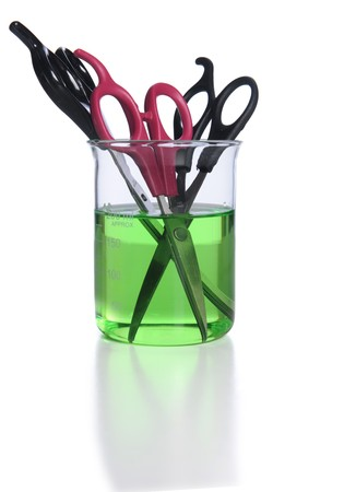 hair cutting scissors in a beaker of green disinfectant