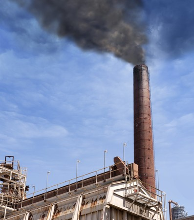 brick chimney of an industrial power plant belches think black smoke against a serene sky