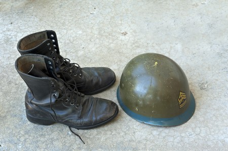 Old American military boots and helmet on concrete