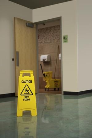 pulizia pavimenti: Un segno di attenzione avverte le persone di un pavimento bagnato davanti alla toilette delle donne  Archivio Fotografico