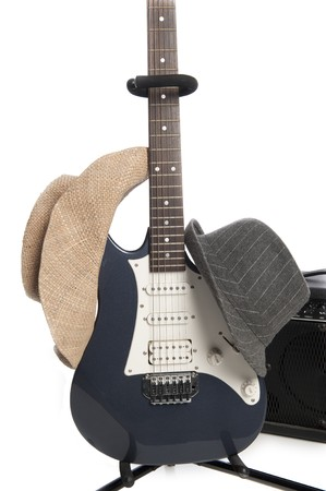 Blue electric guitar on stand with gray mens hat and tan cowboy hat hanging on it