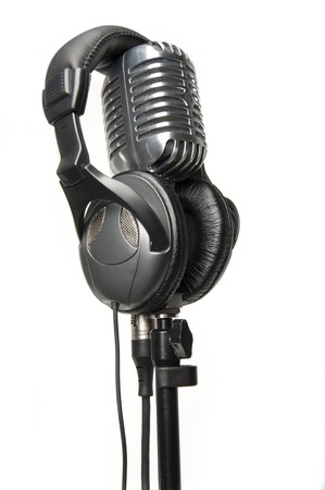 Vintage microphone on stand with a modern pair of headphones on it photo