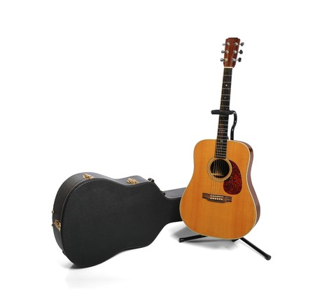 Acoustic guitar and plush case isolated against white background