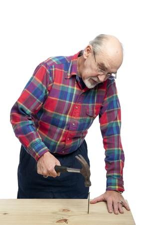 senior citizen drives a nail with a hammer