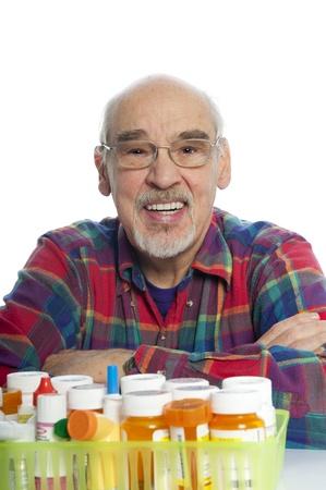 Happy smiling senior citizen reviews his many prescription bottles