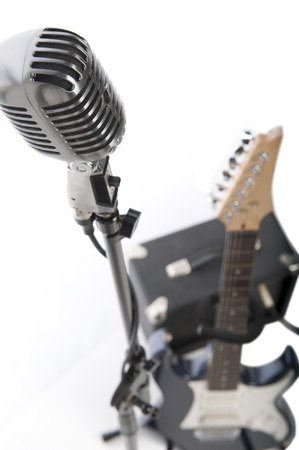 Vintage microphone on stand beside electric guitar and amplifier photo