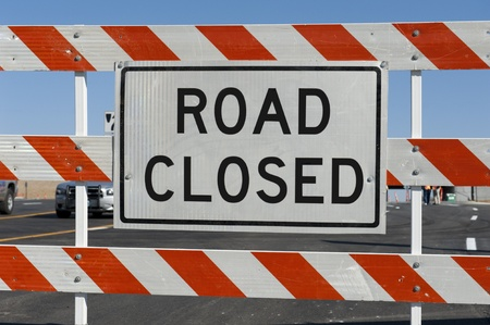 Worn Road Closed Sign in front of street being repaired Stock Photo