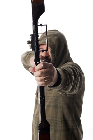 Hooded hunter aims a compound bow and arrow at camera with selective focus on arrowhead Banco de Imagens