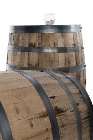 Whiskey glass on wooden barrel, selective focus on glass, isolated on white