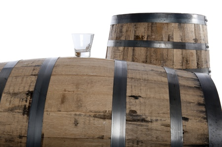 wood barrel: Whiskey glass on a whiskey barrel with a second barrel in the distance, isolated on white, selective focus on glass Stock Photo