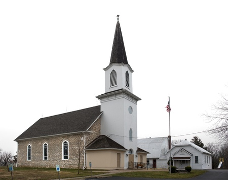 Small country church with white steeple and stone bricks
