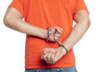 man struggling with handcuffs on his wrists isolated on white background Stock Photo