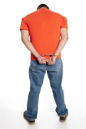 vertical of man in handcuffs on his wrists seen from behind isolated on white