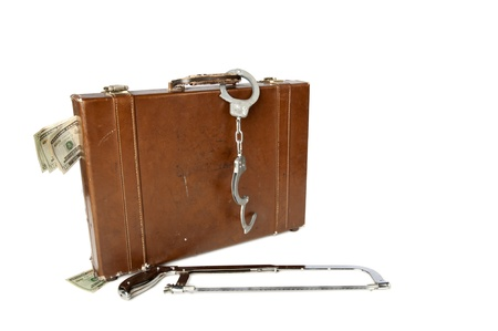 Old leather briefcase with $20 U.S. bills sticking out of it, handcuffs on the handle and a hacksaw in front of it isolated on a white background