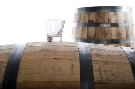Whiskey glass on a whiskey barrel with a second barrel in the distance, isolated on white, selective focus on glass Stock Photo