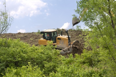 Heavy equipment strips all the vegetation off the side of a hill Stock Photo - 9746867