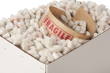 white cardboard box with roll of packing tape inside marked fragile, selective focus on the word fragile