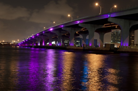 Miami bridge seen from below at night, lit by purple lights photo
