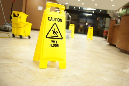 Lobby floor with mop bucket and caution wet floor signs, selective focus on nearest sign photo