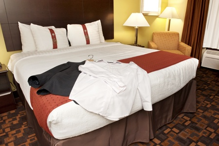 Business suit and shirt on a hotel room bed