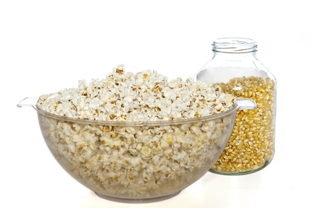 Clear plastic bowl of popcorn and glass jar of unpopped seeds photo