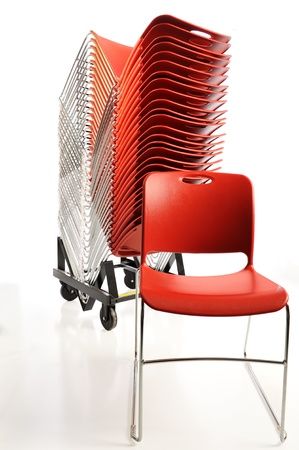 Stack of vibrant orange plastic chairs for a conference