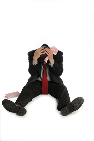 Laid off businessman sits depressed on the floor, isolated on white background