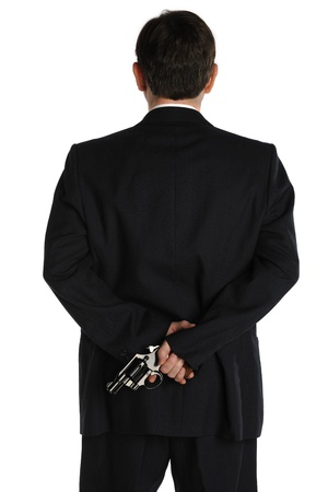 A man in a business suit hides a pistol behind his back