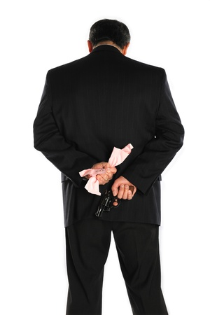 downsized: A man in a business suit hides a pistol behind his back