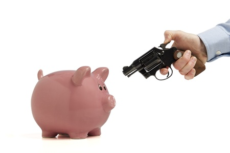 savings problems: Close-up of a piggy bank being robbed by an armed man, isolated on white