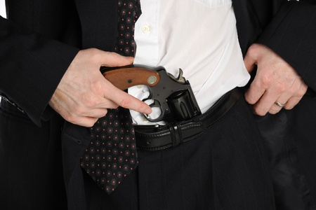Close up of a mans waste, with his hand reaching for a pistol tucked into his pants